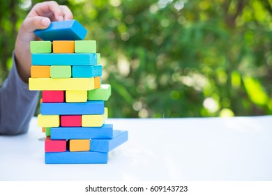 Closeup of asian kid's hand playing colorful wood blocks stack game, education and development concept