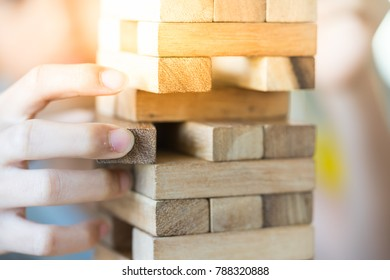 Closeup of asian kid's hand playing wood blocks stack game. Education and development concept.
