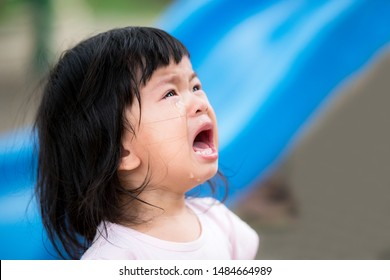 Closeup. Asian little cute girl is crying. She falls on the playgrounds. Baby ages 2 years 6 months. Adorable kid.