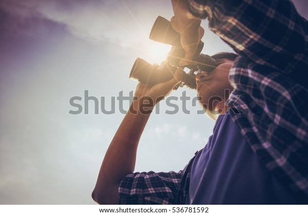 Close-up Of Asian man Hand Holding / looking / watching using Binoculars with copyspace, Technology Binoculars background concept