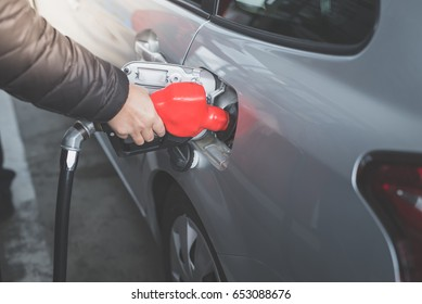 Closeup of Asian man pumping gasoline fuel in car at gas station.