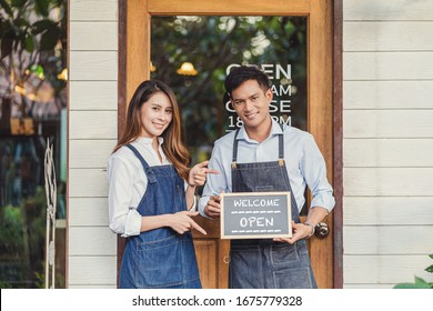 Closeup Asian partner Small business owner hands holding and showing the chalkboard with Welcome Open sign in front of coffee shop, startup with cafe store, installing open and close label concept