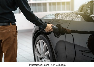 Closeup asian Technician hand is charging the electric car or EV in service center for maintainance, Eco-friendly alternative energy concept