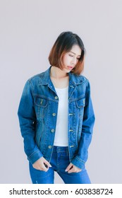 Closeup Asian woman casual outfits standing in jeans and blue denim shirt, women brown hair and short hair, smiling and wearing jeans jacket, beauty and fashion Jeans concept, space wall background
