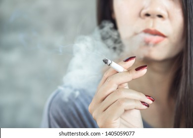 closeup Asian woman hand smoking cigarette ,unhealthy lifestyle concept