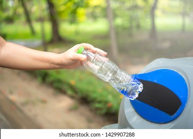 Close-up Asian woman hand throwing empty plastic bottle into the trash.