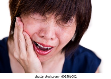 Closeup of Asian woman in intense toothache pain with hands over face