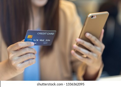 Closeup Asian woman using credit card with mobile for online shopping in department store over the clothes shop store background, technology money wallet and online payment concept, credit card mockup