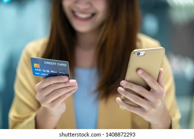 Closeup Asian woman using credit card with mobilephone for online shopping in department store over the clothes shop store, technology money wallet and online payment concept, credit card mockup