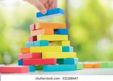 Close-up of asian woman's hand playing colorful wood blocks stack game in morning light with copyspace, playing and learning background concept