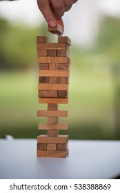 Closeup of asian woman's hand playing wood blocks stack game