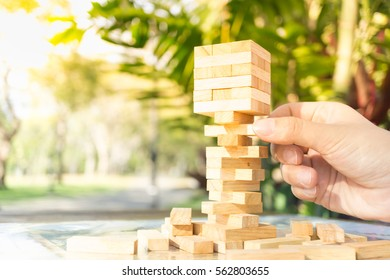 Closeup of asian woman's hand playing wood blocks stack game ,Planning, risk and strategy of project management in business background concept
