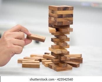 Closeup of asian women's hand playing wood blocks stack game