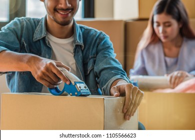 Closeup Asian young couple packing big cardboard box for moving in new house, Moving and House Hunting concept