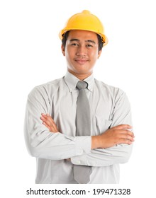 Close-up of an Asian young man wearing a hardhat smiling and looking at camera, arms crossed standing isolated on white background.