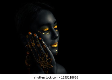 Close-up asian young paint golden on dark skinned, Beauty fashion art portrait with