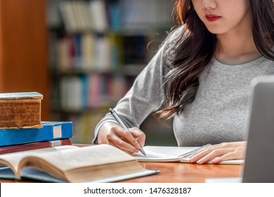 Closeup Asian young Student hand writing homework and using technology laptop in library of university or colleage with various book and stationary over the book shelf background, Back to school