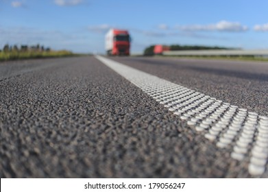 close-up asphalt with dotted white stripe. Red truck on the horizon