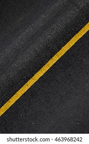 Closeup the asphalt road with yellow straight sign on the street from top view as texture and background , Asphalt Texture and background.