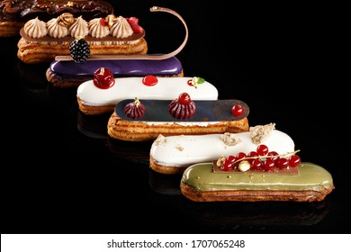 Close-up of Assorted eclairs with cream filling and elegant decorative toppings for confectionary photography concept in black background.