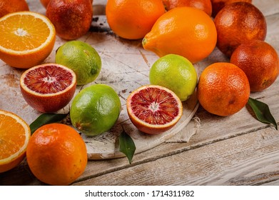 Close-up assorted red oranges, lemons and limes on a wooden table. Seasonal Citrus Fruits