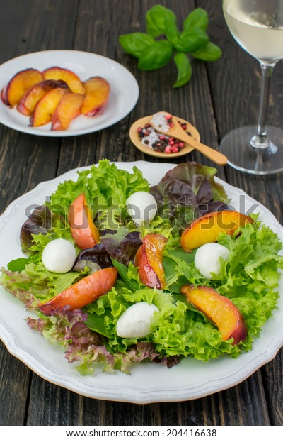 Close-up of assorted salad leaves, grilled peaches and mozzarella salad on a white vintage plate placed on a dark wooden surface; glass of water and fresh basil on the background