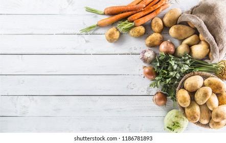 Close-up assortment of fresh vegetables. Potatoes onion carrot celery kohlrabi and garlic on wood.
