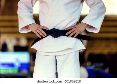 closeup athlete judoka in white kimono and black belt