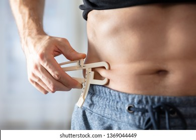 Close-up Of A Athlete Person Measuring His Body Fat With Caliper In The Gym