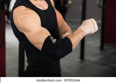 Close-up Of An Athlete Person Wearing Bandage On Elbow In The Gym