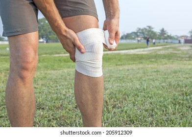 Closeup of athletic male runner wrapping injured left knee with white sports wrap on playing field