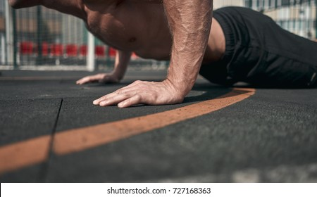 Close-up. Athletic man presses from the floor. Outdoors. Green colors. Sports ground.