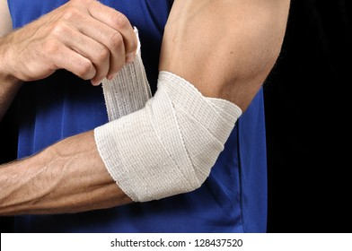 Closeup of athletic man tending injured elbow with sports wrap on black background