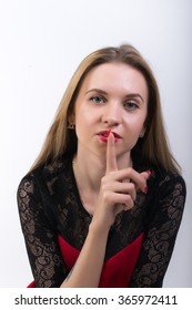 Close-up of attractive brunette woman putting a finger on her lips