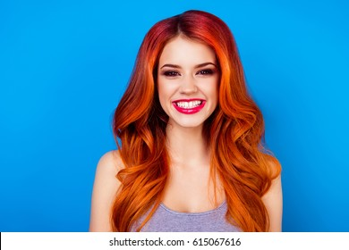 Close-up of attractive cute girl with long ginger fair hair with toothy beaming smile while standing on blue background