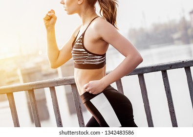 Closeup of attractive fitness woman in stylish sportswear running over bridge in city. Beautiful slender sports girl jogging outdoors. Doing workout, fitness, sport outdoors. Healthy lifestyle