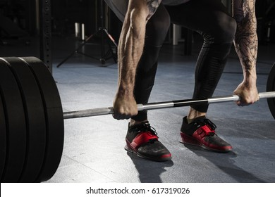 closeup of Attractive muscular bodybuilder preparing to do  deadlifts in modern fitness center.Clean and jerk exercise.Start position