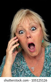 A close-up of an attractive, older blonde woman who is shocked by something she hears on her cellular phone.