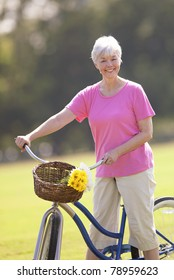 Closeup of attractive older lady on bicycle smiling for camera.