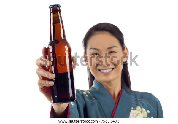 Closeup of attractive smiling kimono woman holding a bottle of beer isolated over white background