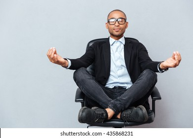Closeup of attractive young man in glasses meditating on office chair