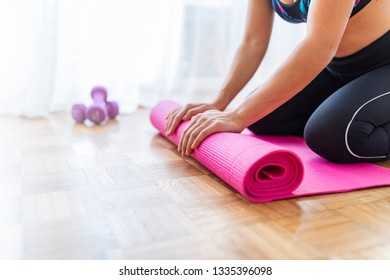 Close-up of attractive young woman folding pink yoga or fitness mat after working out at home in living room.  Equipment for fitness, pilates, yoga. Concept of well being