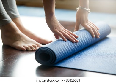 Close-up of attractive young woman folding blue yoga or fitness mat after working out at home in living room. Healthy life, keep fit concepts. Horizontal shot