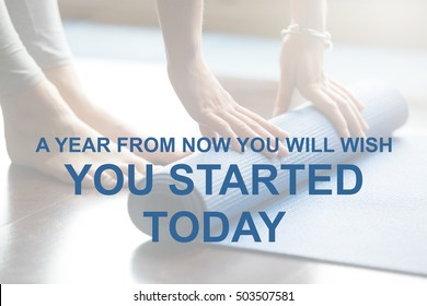 """Close-up of attractive young woman folding blue yoga or fitness mat after working out at home. Healthy life, keep fit concepts. Motivational text """"A year from now you will wish you started today"""""""
