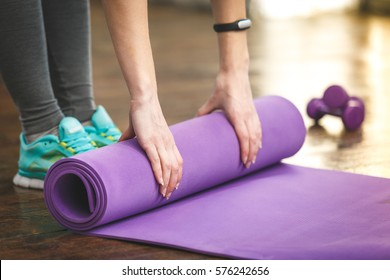 Close-up of attractive young woman folding yoga or fitness mat after working out at home in living room. Healthy life, keep fit concepts. Horizontal shot