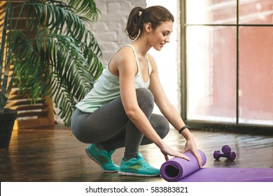Close-up of attractive young woman folding yoga or fitness mat after working out at home in living room. Healthy life, keep fit concepts.