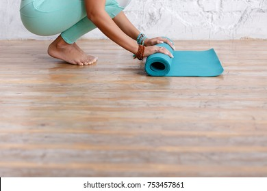 Close-up of attractive young woman folding blue yoga or fitness mat after working out at home in living room. Yoga and healthy lifestyle concept. Horizontal shot. white loft studio