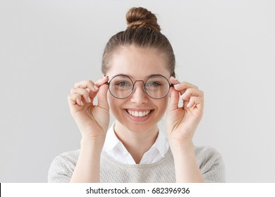 Closeup of attractive young woman isolated on gray background, wearing big round spectacles with thin black frame, touching temples with fingers, smiling with expression of satisfaction and interest.