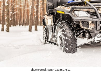 Close-up ATV 4wd quad bike in forest at winter. 4wd all-terreain vehicle stand in heavy snow with deep wheel track. Seasonal extreme sport adventure and trip. Copyspace
