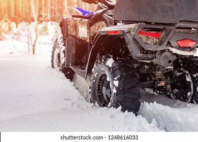 Close-up ATV 4wd quad bike in forest at winter. 4wd all-terreain vehicle stand in heavy snow with deep wheel track. Seasonal extreme sport adventure and trip. Copyspace.
